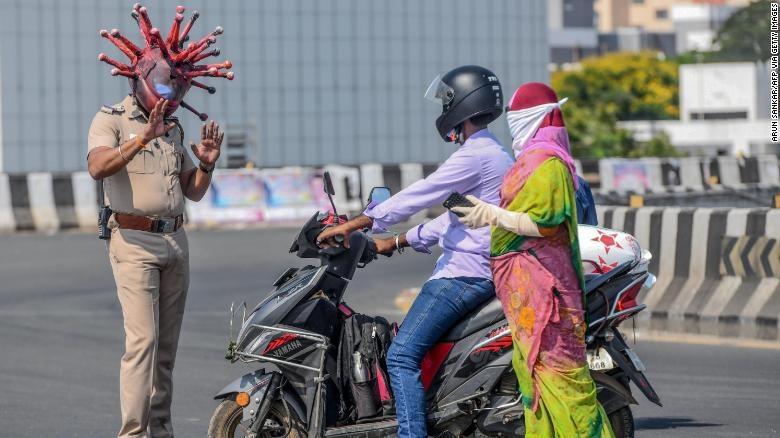 Một sĩ quan cảnh sát  đội mũ bảo hiểm coronavirus để cảnh báo mọi người; ở lại bên trong khi Ấn Độ đóng cửa