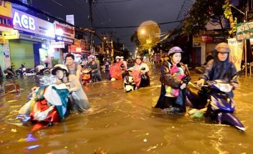 [Ảnh] Đường phố TPHCM ngập sâu sau mưa lớn chiều cuối tuần, người dân người lội nước về nhà